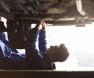 A mechanic fixing a car followign a breakdown. Talk to CSW Insurance Brokers to arrange breakdown insurance cover today.