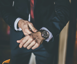 A man in a suit putting on his new watch. At CSW Insurance Brokers we can cover watches and other expensive belongings with a high net worth insurance policy.