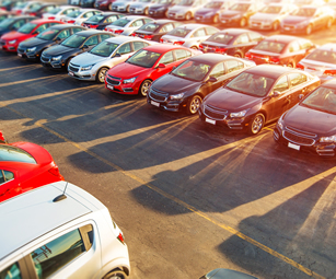 Rows of new cars at a car dealership. A motor trade insurance policy arranged by CSW insurance brokers could cover your garage.